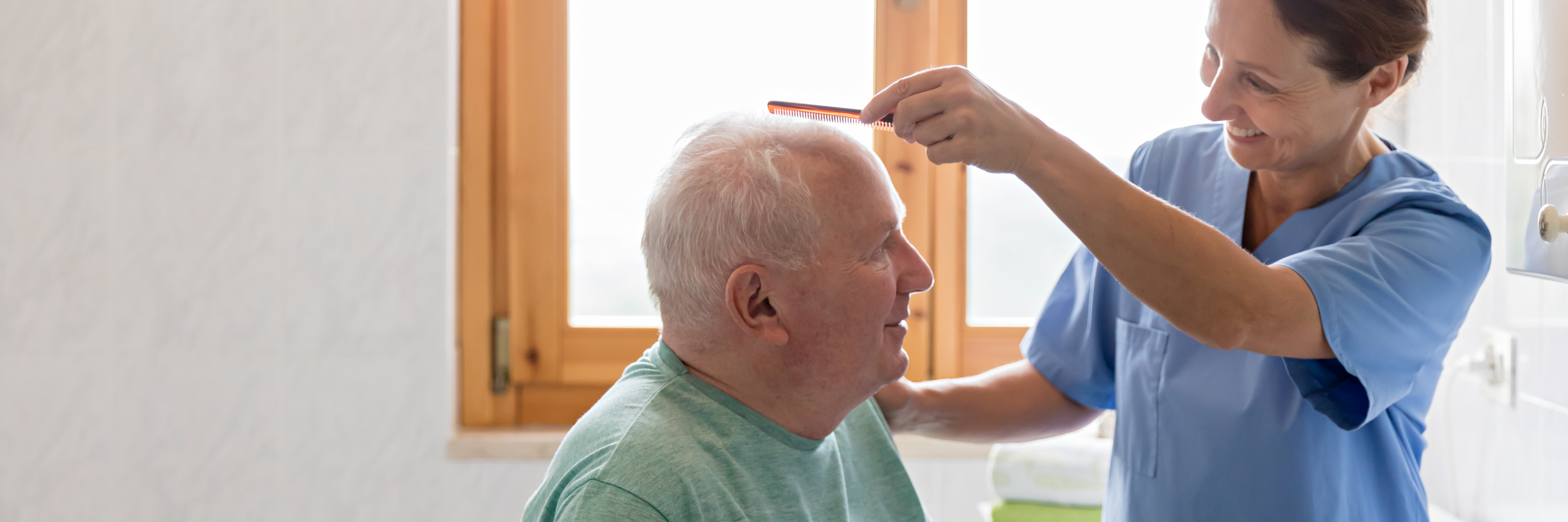 Female nurse combing older man's hair